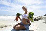 Portrait of smiling pregnant woman on the beach holding carrots and beetroot - ECPF00303