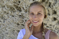 Portrait of smiling blond woman with rocky background - ECPF00309