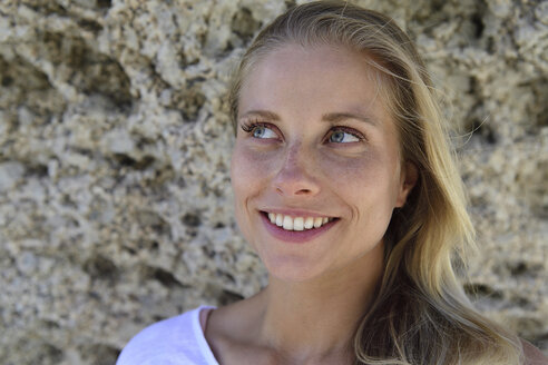Portrait of smiling blond woman with rocky background - ECPF00312