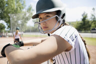 Serious middle school girl softball player wearing batting helmet watching game - HEROF13554