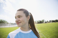Smiling middle school girl soccer player looking away on sunny field - HEROF13563