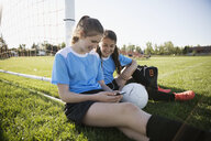 Smiling middle school girl soccer teammates with mp3 player sharing music - HEROF13566