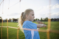 Serious middle school girl soccer player stretching at goal net - HEROF13569