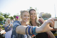 Smiling young women taking selfie at summer music festival campsite - HEROF13578