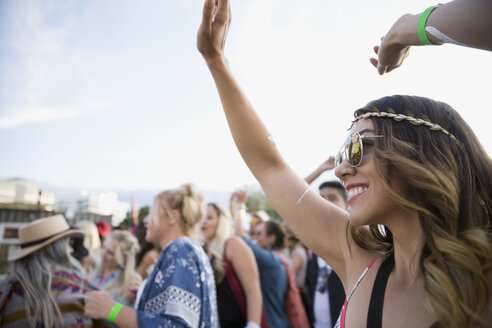 Smiling young woman cheering in crowd at summer music festival - HEROF13581