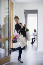 Smiling businesswoman returning home with groceries and flowers closing door with foot in foyer - HEROF13584