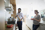Pregnant couple cooking pasta in kitchen - HEROF13593
