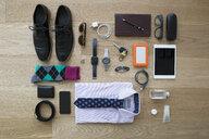 Still life business travel items on hardwood floor - HEROF13611