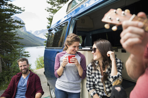 Smiling women drinking coffee and talking at camper van at lakeside - HEROF13638