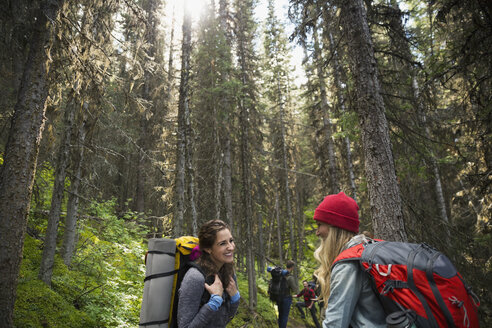 Smiling women hiking with on trail in woods - HEROF13641