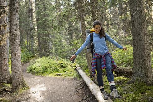 Smiling woman hiking walking along fallen tree in woods - HEROF13644