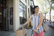 Smiling woman walking bicycle along urban sidewalk outside storefront - HEROF13653