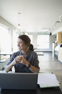 Smiling female cafe owner drinking coffee at laptop - HEROF13656