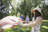 Smiling woman laying blanket for picnic in sunny summer park - HEROF13665