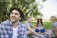 Smiling man with friends in summer park - HEROF13668
