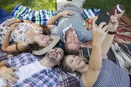 Smiling couples taking selfie on blanket in park - HEROF13671