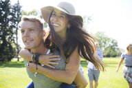 Smiling couple piggybacking in sunny summer park - HEROF13674