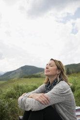 Serene woman relaxing in remote rural field - HEROF13677