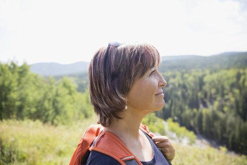 Serene woman with backpack hiking on sunny rural hillside - HEROF13689