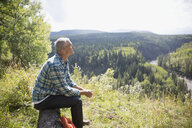 Serene man hiking resting on log at sunny remote rural hilltop - HEROF13692