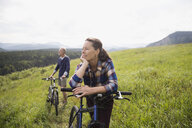 Senior couple with mountain bikes in sunny remote rural field - HEROF13704
