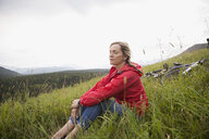 Serene woman relaxing in grass near mountain bike in rural field - HEROF13707