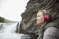 Serene woman listening to headphones with music at waterfall - HEROF13716