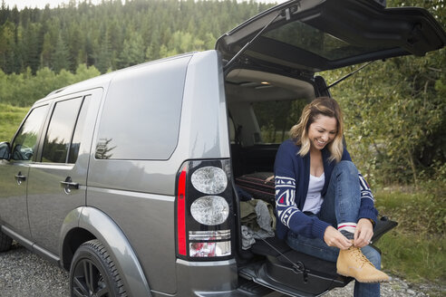 Smiling woman putting on hiking shoes at back of SUV - HEROF13719
