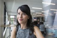 Portrait pensive businesswoman looking away in office - HEROF13722