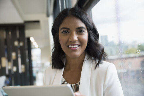 Portrait smiling businesswoman with digital tablet at office window - HEROF13731
