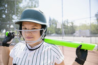 Portrait smiling middle school girl softball player ready to bat - HEROF13734