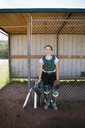 Portrait serious middle school girl softball catcher at dugout fence - HEROF13737