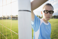 Portrait serious middle school girl soccer player wearing goggles showing attitude at goal net post - HEROF13743