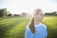 Portrait pensive middle school girl soccer player looking away on sunny y field - HEROF13746