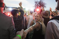 Portrait smiling young couple holding hands in crowd at summer music festival - HEROF13755