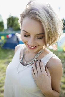 Portrait smiling young blonde woman at summer music festival campsite - HEROF13767