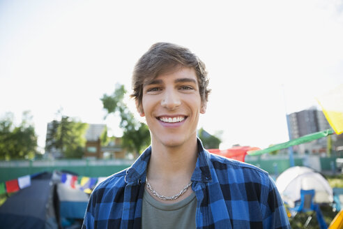 Portrait smiling young brunette man at summer music festival campsite - HEROF13770