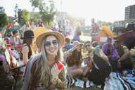 Portrait smiling young woman drinking with friends at summer music festival campsite - HEROF13773