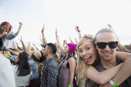 Portrait playful young couple in crowd at summer music festival - HEROF13776