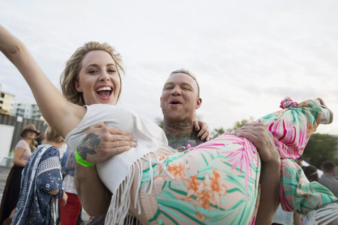 Portrait playful young man carrying exuberant girlfriend at summer music festival - HEROF13779