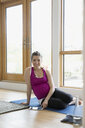 Portrait smiling pregnant woman with digital tablet practicing yoga on floor - HEROF13785
