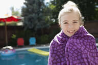 Portrait smiling girl wrapped in a towel at sunny poolside - HEROF13800