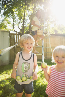 Portrait smiling family gathering apples in sunny backyard - HEROF13815