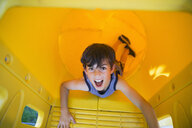 Portrait playful boy inside yellow playground slide - HEROF13821