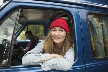 Portrait smiling woman leaning on window of camper van - HEROF13833