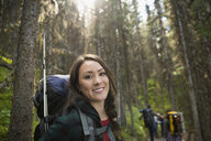 Portrait smiling woman hiking with backpack in woods - HEROF13839