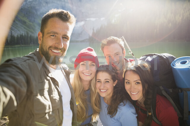 Portrait smiling friends hiking taking selfie at sunny lakeside - HEROF13842