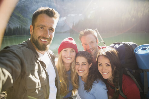 Portrait smiling friends hiking taking selfie at sunny lakeside - HEROF13842
