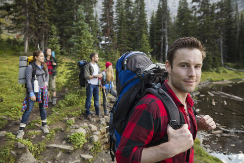 Portrait smiling man with backpack hiking with friends in woods - HEROF13845