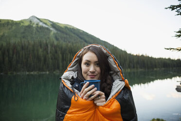 Portrait smiling woman drinking coffee standing in sleeping bag at remote lakeside - HEROF13848